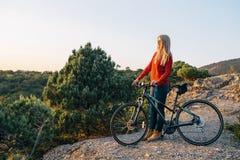 Junge blonde Frau steht mit Fahrrad auf Gebirgsstraße und vorwärts -schauen Stockfotos