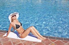Junge blonde Frau am Swimmingpool Lizenzfreie Stockfotografie
