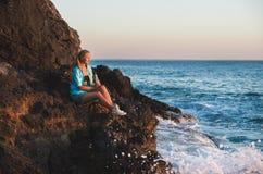 Junge blonde Frau touristisches sittig auf Felsen durch das Meer bei Sonnenuntergang mit Flasche Limonade Alanya, Mittelmeerregio Stockfoto