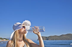 Junge blonde Frau trinkt Wasser Stockbild