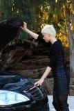 Junge blonde Frau und defektes Auto Stockbild