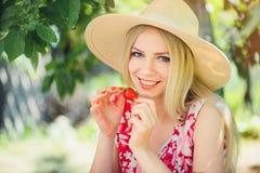 Junge blonde Frau, welche die Erdbeeren lächeln am sonnigen Tag des Gartensommers, am warmen Sommer Bild tonend, an der Selbsthil Lizenzfreies Stockfoto
