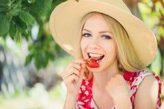 Junge blonde Frau, welche die Erdbeeren lächeln am sonnigen Tag des Gartensommers, am warmen Sommer Bild tonend, an der Selbsthil Lizenzfreies Stockbild