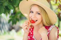 Junge blonde Frau, welche die Erdbeeren lächeln am sonnigen Tag des Gartensommers, am warmen Sommer Bild tonend, an der Selbsthil Lizenzfreie Stockfotografie
