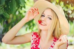 Junge blonde Frau, welche die Erdbeeren lächeln am sonnigen Tag des Gartensommers, am warmen Sommer Bild tonend, an der Selbsthil Lizenzfreie Stockfotos