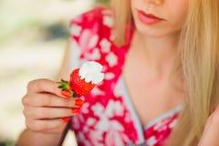 Junge blonde Frau, welche die Erdbeeren lächeln am sonnigen Tag des Gartensommers, am warmen Sommer Bild tonend, an der Selbsthil Lizenzfreie Stockbilder