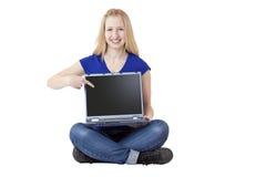Junge, blonde Frau zeigt mit dem Finger auf Laptop Stockfoto
