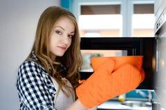 Junge blonde Frau zieht eine heiße Schüssel von der Mikrowelle aus Lizenzfreie Stockbilder