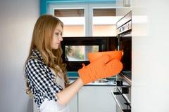 Junge blonde Frau zieht eine heiße Schüssel von der Mikrowelle aus Lizenzfreie Stockfotos