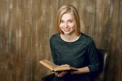 Junge blonde Frau zu Hause, Lesebuch Hölzerner Wanddachbodenhintergrund Lizenzfreie Stockbilder