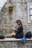 Junge blonde gelockte behaarte Schönheit, die ein eBook in O liest Stockfoto