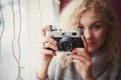Junge blonde gelockte Frau in der Strickjacke mit alter Filmkamera Lizenzfreie Stockbilder