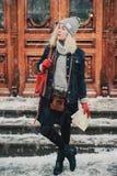 Junge blonde gelockte Frau mit alter Filmkamera und -karte Lizenzfreie Stockbilder