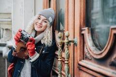Junge blonde gelockte Frau mit der alten Filmkamera, lächelnd, Winter Stockfotos