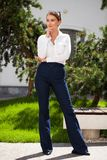 Junge blonde Geschäftsfrau in den Blue Jeans und im weißen Hemd lizenzfreies stockbild