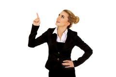 Junge blonde Geschäftsfrau, die auf etwas zeigt Lizenzfreie Stockbilder