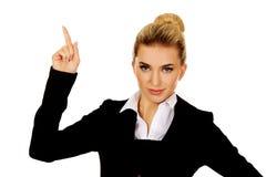 Junge blonde Geschäftsfrau, die auf etwas zeigt Stockbilder