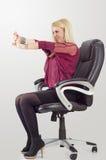 Junge blonde Geschäftsfrau, die das Ausdehnen, beim Sitzen im Stuhl tut Lizenzfreies Stockbild