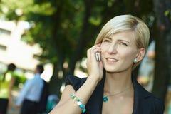 Junge blonde Geschäftsfrau, die am Handy spricht Stockfotos