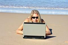 Junge blonde Geschäftsfrau, die an ihrem Laptop arbeitet Stockbild