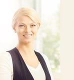 Junge blonde Geschäftsfrau, die im Büro arbeitet Stockbild