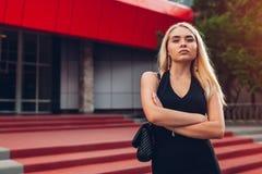 Junge blonde Geschäftsfrau, die modernes Geschäftszentrum in der Stadt mit den Händen gekreuzt bereitsteht stockbilder