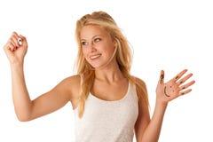 Junge blonde Geschäftsfrau mit blauen Augen, schreibt auf ein Glas ta Stockfoto
