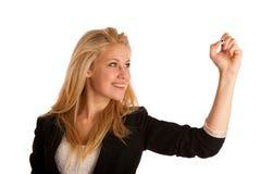 Junge blonde Geschäftsfrau mit blauen Augen, schreibt auf ein Glas ta Lizenzfreies Stockbild