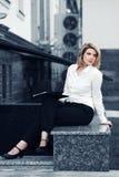 Junge blonde Geschäftsfrau mit einem Ordner Stockbild