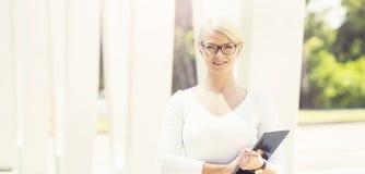 Junge blonde Geschäftsfrau mit einer Tablette draußen Stockfotos