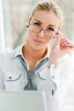Junge blonde Geschäftsfrau mit Gläsern unter Verwendung Laptop PC nahe Fenster in ihrem Büro Lizenzfreies Stockfoto