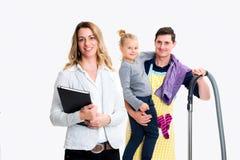 Junge blonde Geschäftsfrau und ihr Ehemann mit Kind im backgrou Lizenzfreies Stockfoto