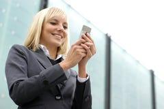 Junge blonde Geschäftsfrau wählt das Telefon Lizenzfreie Stockfotografie