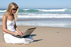 Junge blonde Geschäftsfrau, die an ihrem Laptop arbeitet Stockfotos