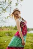 Junge blonde hübsche Dame in den grünen und roten sundress Stockfotografie