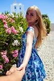 Junge blonde hübsche Frau in einem weißen und blauen Kleid über Mittelmeeransicht Stockbilder