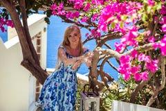 Junge blonde hübsche Frau in einem weißen und blauen Kleid über Mittelmeeransicht Stockfoto