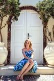 Junge blonde hübsche Frau in einem weißen und blauen Kleid über Mittelmeeransicht Lizenzfreie Stockfotos