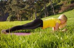 Junge blonde Handelnplankenübung draußen Stockfoto