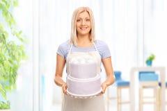 Junge blonde Hausfrau, die einen großen Kuchen hält Lizenzfreie Stockfotografie