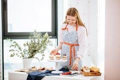 Junge blonde Hausfrau, die kleine Kuchen mit Beeren auf der Umhüllungsservierplatte im Kochen verziert Stockfotografie