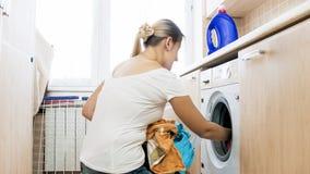 Junge blonde Hausfrau, die schmutzige Kleidung in der Waschmaschine lädt Stockbild