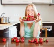 Junge blonde Hausfrau mit Erdbeeren Stockfotos