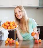 Junge blonde Hausfrau mit Haufen der inländischen Küche der Aprikosen t Lizenzfreie Stockfotos