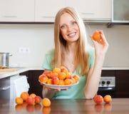 Junge blonde Hausfrau mit Haufen der inländischen Küche der Aprikosen t Stockfotos