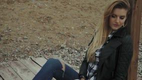 Junge blonde hübsche Frau, die auf hölzernem Pier und dem Stillstehen sitzt stock footage