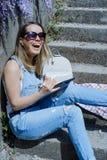 Junge blonde Hippie-Frau in der Sonnenbrille zeichnet auf eine Tablette in SU Lizenzfreie Stockfotografie