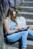 Junge blonde Hippie-Frau in der Sonnenbrille zeichnet auf eine Tablette in SU Lizenzfreie Stockbilder