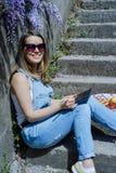 Junge blonde Hippie-Frau in der Sonnenbrille zeichnet auf eine Tablette in SU Lizenzfreies Stockfoto