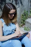 Junge blonde Hippie-Frau in der Sonnenbrille zeichnet auf eine Tablette in SU Stockfotografie
